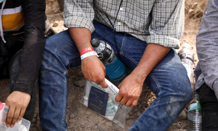 An illegal immigrant wears two wristbands that Mexican cartels have been using to control human smuggling into the United States, near Penitas, Texas, on March 15. 2021. (Charlotte Cuthbertson/The Epoch Times)