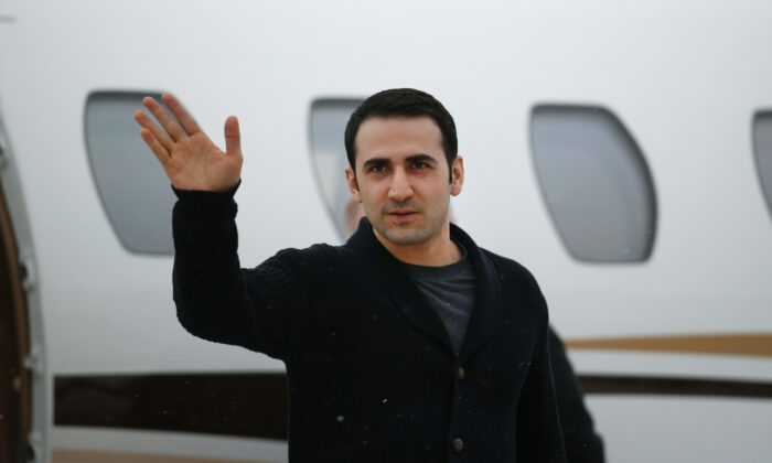 Amir Hekmati waves after arriving on a private flight at Bishop International Airport in Flint, Mich., on Jan. 21, 2016. (Paul Sancya/AP Photo)