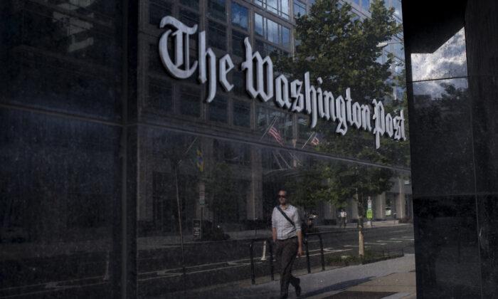 A man walks past The Washington Post in Washington on Aug. 5, 2013. (Brendan Smialowski/AFP via Getty Images)