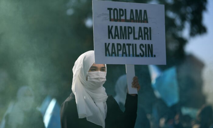 "A woman holds a placard reading ""Close the camps"" during a demonstration by supporters of China's Muslim Uyghur minority against China's Uighur treatment at the Beyazid square in Istanbul, Turkey, on Oct. 1, 2020. (Ozan Kose/AFP via Getty Images)"