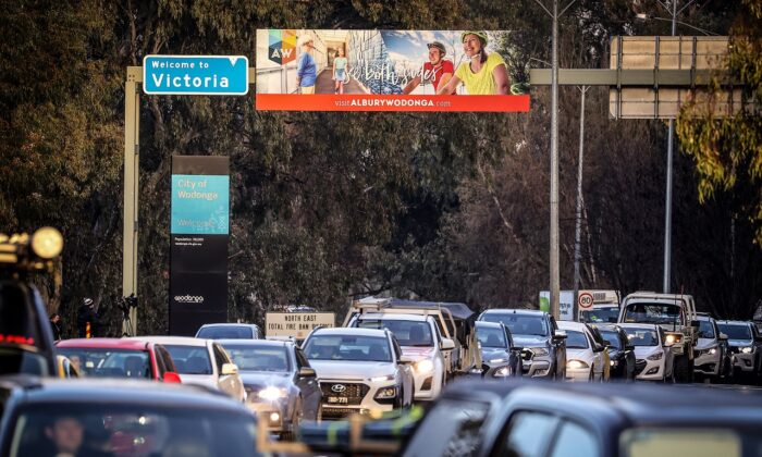 Cars sit in a line underneath a sign regarding the NSW-Victorian border near a police checkpoint in Albury, Australia, on July 8, 2020. ( David Gray/Getty Images)