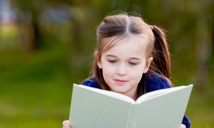Young child reading a book (First Glimpse Photography/Shutterstock)
