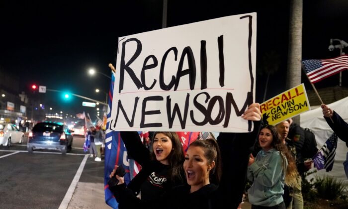 Trump supporters shout slogans while carrying a sign calling for a recall on California Gov. Gavin Newsom during a protest against a stay-at-home order amid the COVID-19 pandemic in Huntington Beach, Calif., on Nov. 21, 2020. (Marcio Jose Sanchez/AP Photo)