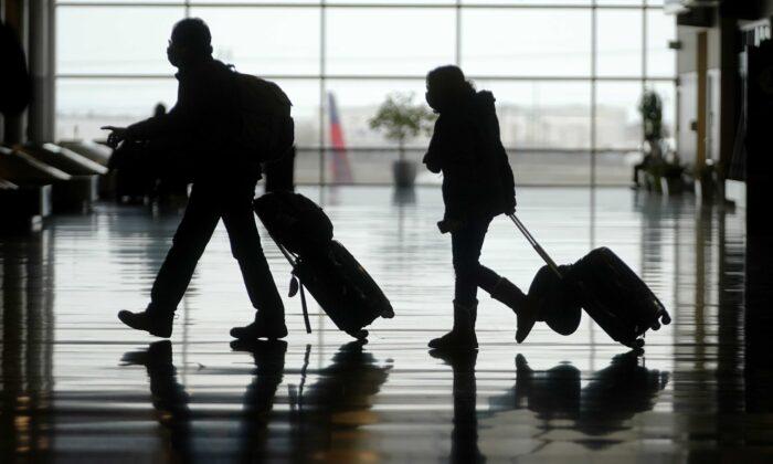 Travelers walk through the Salt Lake City International Airport, in Salt Lake City on March 9, 2021. (Rick Bowmer/AP Photo)