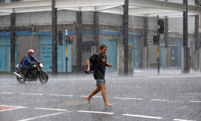 A boy runs for cover through the heavy rain in the central business districk of Sydney on Mar. 2, 2017. (SAEED KHAN/AFP via Getty Images)