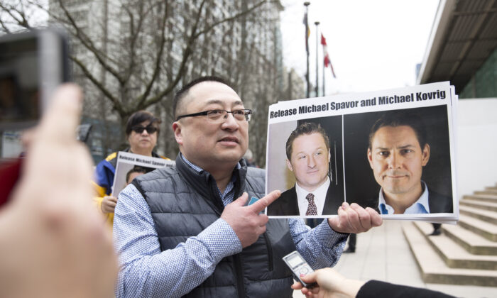 Louis Huang of Vancouver Freedom and Democracy for China holds photos of Canadians Michael Spavor and Michael Kovrig, who are being detained in China, outside the B.C. Supreme Court in Vancouver on March 6, 2019. (Jason Redmond/AFP)