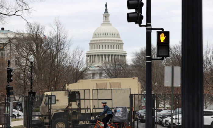 An eight-foot-tall security fence topped with concertina razor wire surrounds the U.S. Capitol and National Guard vehicles are parked inside the temporary perimeter in Washington, on March 16, 2021. (Chip Somodevilla/Getty Images)