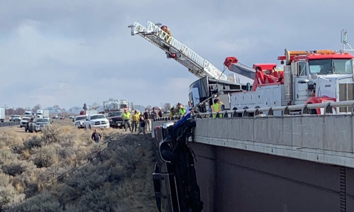 Emergency crews rescue two people after their pickup truck plunged off a bridge, leaving them dangling above a deep gorge in southern Idaho, on March 15, 2021. (Idaho State Police via AP)