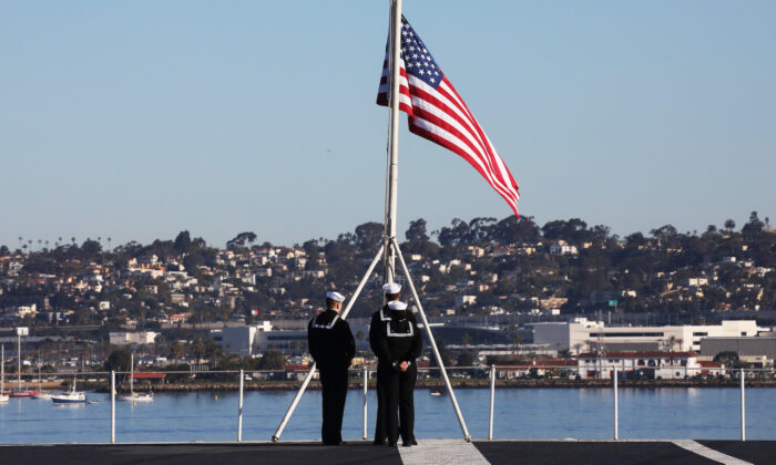 U.S. Navy sailors prepare to take down the flag on the flight deck of the USS Nimitz aircraft carrier in Coronado, Calif., on Jan. 18, 2020. (Mario Tama/Getty Images)