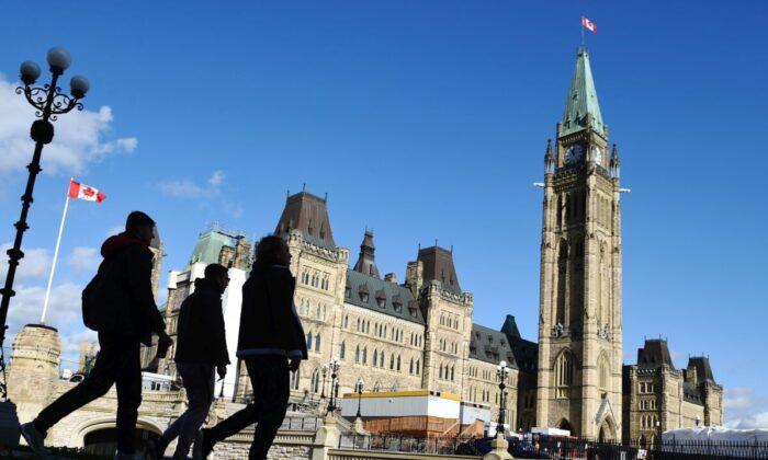 People walk past Parliament Hill in Ottawa on Oct. 23, 2019. (The Canadian Press/Sean Kilpatrick)