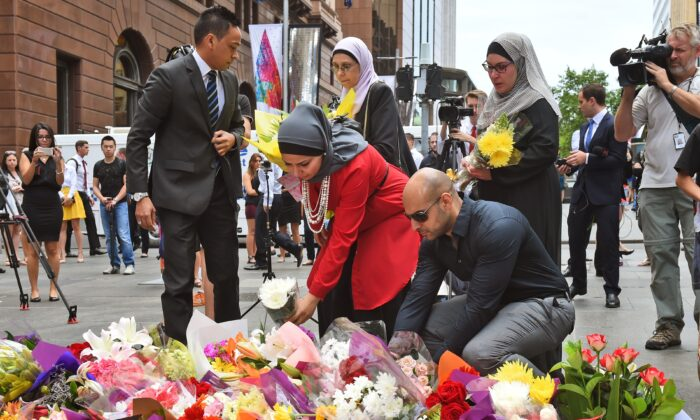 Representatives of the Muslim community lay flowers at a floral memorial at the scene of a dramatic siege by Islamic extremist Man Haron Monis which left two hostages dead (William West/AFP via Getty Images)