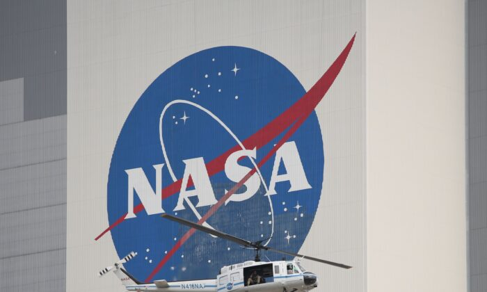 A NASA security helicopter flies past the Vehicle Assembly Building on launch day at the Kennedy Space Center in Florida on May 26, 2020. (Gregg Newton/AFP via Getty Images)