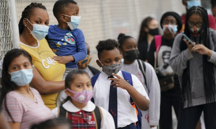 Students wear protective masks as they arrive for classes at the Immaculate Conception School while observing COVID-19 prevention protocols in The Bronx borough of New York on Sept. 9, 2020. (John Minchillo/AP Photo)