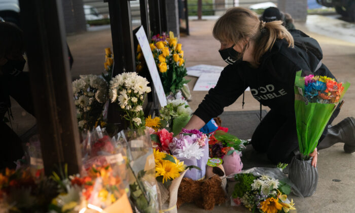 Shelby Swan adjusts flowers and signs outside Youngs Asian Massage where four people were shot and killed, in Acworth, Ga., on March 17, 2021. (Elijah Nouvelage/Getty Images)