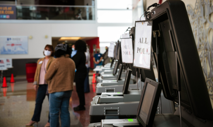 Election officials speak amongst themselves near electronic ballot boxes in the polling area in the KFC YUM! Center in Louisville, Kentucky, on Nov. 3, 2020. (Jon Cherry/Getty Images)