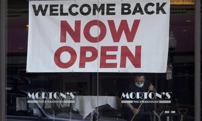 "A sign reading ""Welcome Back Now Open"" is posted on the window of a Morton's Steakhouse restaurant as a man works inside during the COVID-19 pandemic in San Francisco, Calif., on March 4, 2021. (Jeff Chiu/File Photo via AP)"