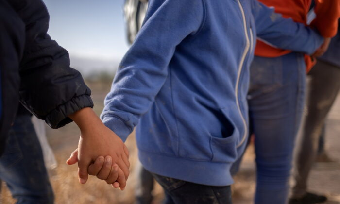 Unaccompanied minors hold hands as they await transport after crossing the Rio Grande river into the United States from Mexico on a raft in Penitas, Texas, on March 12, 2021. (Adrees Latif/Reuters)