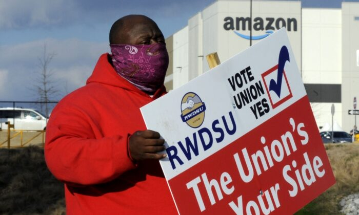 Michael Foster of the Retail, Wholesale and Department Store Union holds a sign outside an Amazon facility where labor is trying to organize workers in Bessemer, Ala., on Feb. 9, 2021. (Jay Reeves/AP Photo)