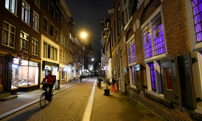 A cyclist drives down a street ahead of a curfew following the coronavirus disease (COVID-19) outbreak in Amsterdam, Netherlands, on Jan. 23, 2021. (Piroschka Van De Wouw/Reuters)