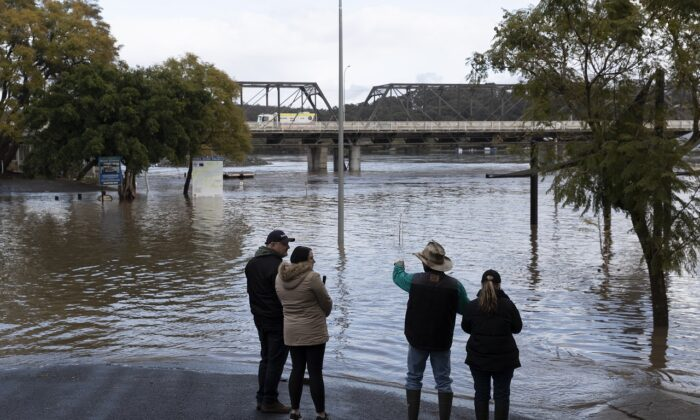 People look on as heavy flooding is seen along the Shoalhaven River in NSW, Australia, on Aug. 10, 2020. (Brook Mitchell/Getty Images)