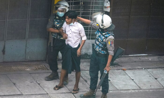Riot police officers detain a demonstrator during a protest against the military coup in Yangon, Burma, on March 19, 2021. (Stringer/Reuters)