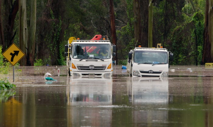 A still image taken from video shows trucks stuck in a flooded road, following heavy rains in Taree, New South Wales, Australia March 20, 2021. (NSW State Emergency Service via Reuters)