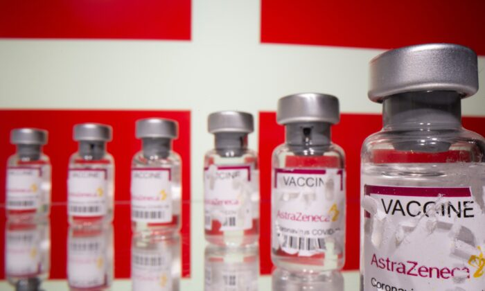 "Vials labelled with broken sticker ""AstraZeneca COVID-19 Coronavirus Vaccine"" are seen in front of a displayed Denmark flag in this illustration taken on March 15, 2021. (Dado Ruvic/Illustration/Reuters)"