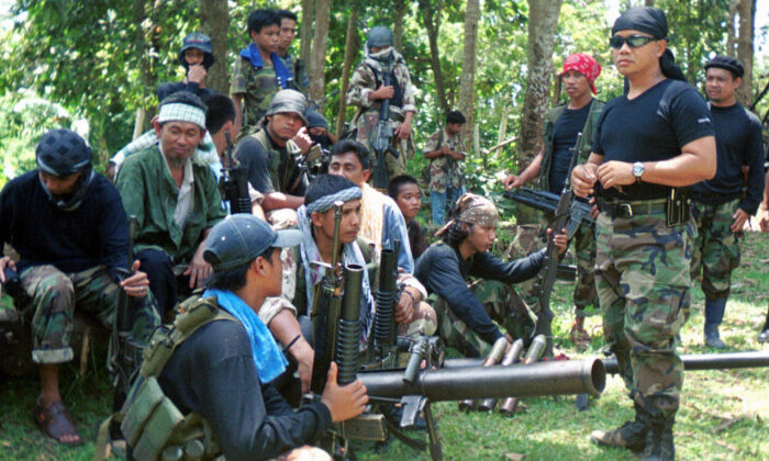 Abu Sayyaf spokesman Abu Sabaya, right foreground, is seen with his band of armed extremists. Philippine troops captured an Abu Sayyaf rebel commander blamed for years of ransom kidnappings and rescued the last of his four Indonesian captives on Sunday, March 21, 2021. (AP Photo, File)