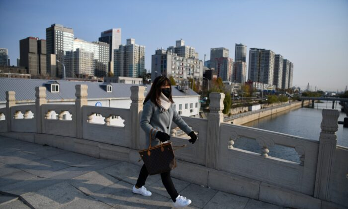 A woman crosses a bridge near apartment and office complexes in Beijing, China, on Dec. 1, 2020.(Greg Baker/AFP via Getty Images)