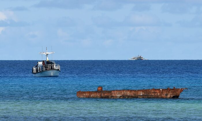 A research boat (L) and Filipino fishing boat (back R) anchored near Thitu island in the disputed Spratly islands of the South China Sea on April 21, 2017. (TED ALJIBE/AFP via Getty Images)