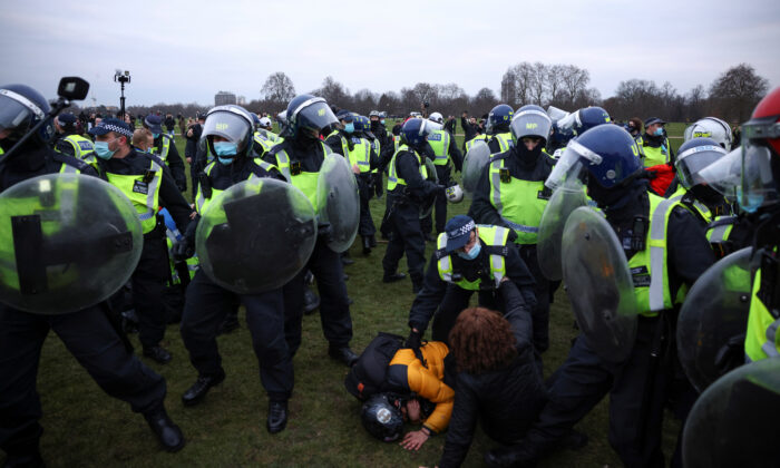 Police officers detain people during a protest against CCP virus lockdown in London, on March 20, 2021. (Henry Nicholls/Reuters)