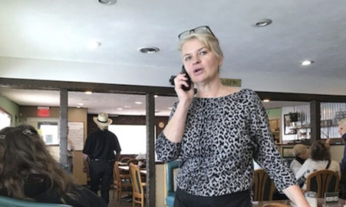 Marlena Pavlos-Hackney talks on a cell phone at her restaurant Marlena's Bistro & Pizzeria, in Holland, Mich., on March 18, 2021. Michigan State Police arrested Pavlos-Hackney on March 19, 2021. (John Agar/The Grand Rapids Press via AP)