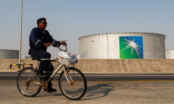 An employee rides a bicycle next to oil tanks at Saudi Aramco oil facility in Abqaiq, Saudi Arabia, on Oct. 12, 2019. (Maxim Shemetov/Reuters)