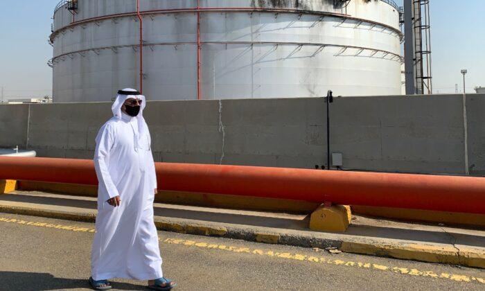 A man, mask-clad due to the COVID-19 coronavirus pandemic, walks past a damaged silo at the Saudi Aramco oil facility in Saudi Arabia's Red Sea city of Jeddah, on Nov. 24, 2020. (Fayez Nureldine/AFP via Getty Images)