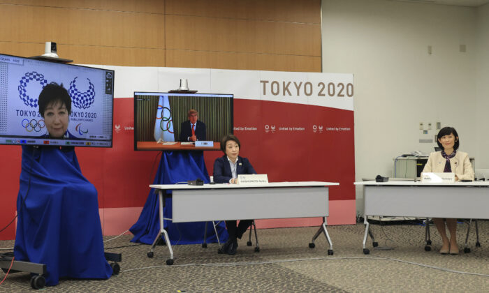 International Olympic Committee (IOC) President Thomas Bach, on right screen, delivers an opening speech while Tokyo 2020 Organizing Committee president Seiko Hashimoto, front left, Tokyo Gov. Yuriko Koike, on left screen, and Japanese Olympic Minister Tamayo Marukawa listen at a five-party meeting of Tokyo 2020 Olympic and Paralympic Games with International Paralympic Committee (IPC) President Andrew Parsons in Tokyo on March 20, 2021. (Yoshikazu Tsuno/Pool Photo via AP)