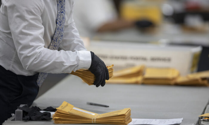 A worker with the Detroit Department of Elections helps sort through absentee ballots at the Central Counting Board in the TCF Center in Detroit, Mich., on Nov. 4, 2020. (Elaine Cromie/Getty Images)