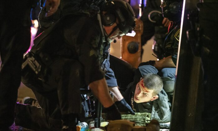 Portland police officers and Oregon state troopers arrest a man they said was armed with a rifle during a protest in Portland, Ore., on Nov. 4, 2020. (Nathan Howard/Getty Images)