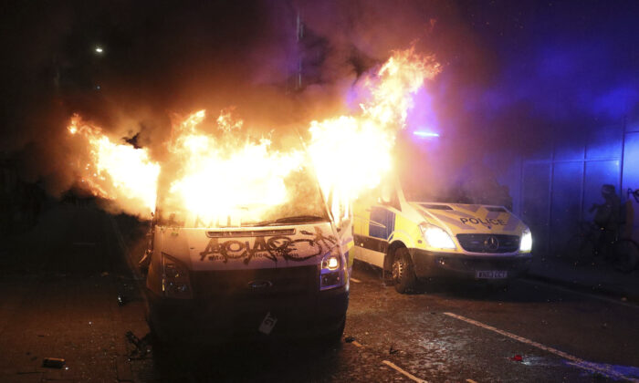 A vandalised police van on fire outside Bridewell Police Station, in Bristol, England, on March 21, 2021. (Andrew Matthews/PA via AP)