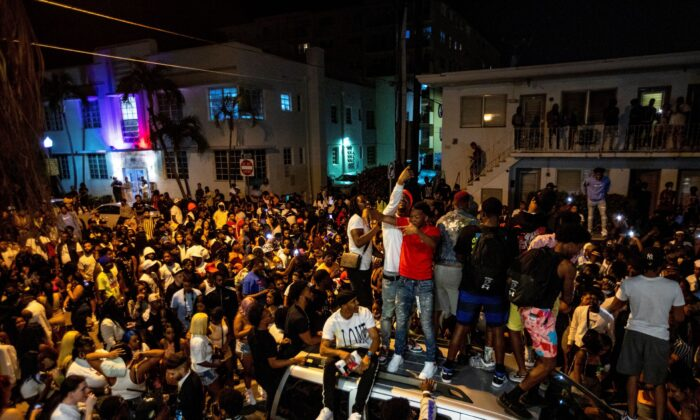 Crowds defiantly gather in the street while a speaker blasts music an hour past curfew in Miami Beach, Fla., on March 21, 2021. (Daniel A. Varela/Miami Herald via AP)