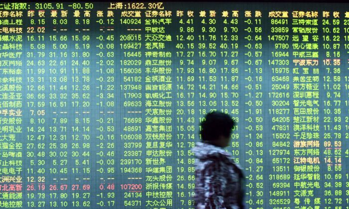 An investor walks past a screen showing stock market movements at a securities firm in Hangzhou, China on Jan. 11, 2016.  (STR/AFP via Getty Images)