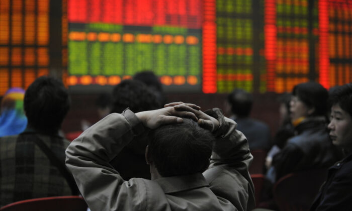 Investors watch an electronic board showing stock prices at a securities brokerage in Beijing on March 20, 2008. (Peter Parks/AFP via Getty Images)