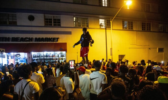 A man stands on a car as crowds defiantly gather in the street while a speaker blasts music an hour past curfew in Miami Beach, Fla., on March 21, 2021. (Daniel A. Varela/Miami Herald via AP)