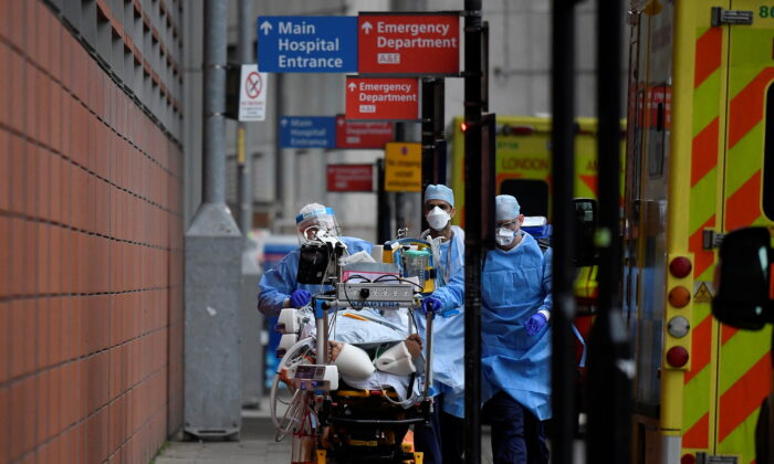Medical workers move a patient between ambulances outside of the Royal London Hospital amid the spread of the COVID-19 pandemic in London on Jan. 27, 2021. (Toby Melville/Reuters)