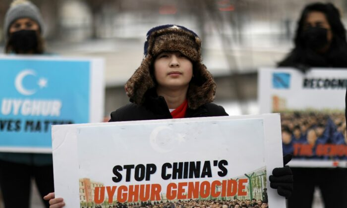 People take part in a rally to encourage Canada and other countries as they consider labelling China's treatment of its Uyghur population and Muslim minorities as genocide, outside the Canadian Embassy in Washington on Feb. 19, 2021. (Reuters/Leah Millis)