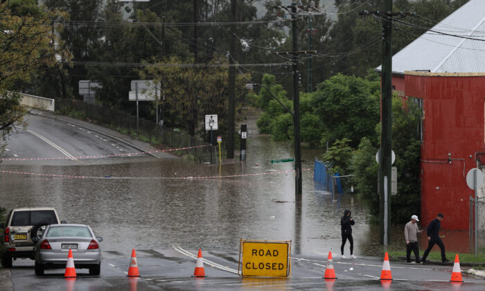 People walk on a street inundated with floodwaters in the suburb of Windsor as the state of New South Wales experiences widespread flooding and severe weather, in Sydney, Australia, on March 22, 2021. (Loren Elliott/Reuters)