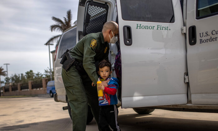 A Border Patrol agent delivers a family unit who illegally entered the United States to a bus station in Brownsville, Texas on Feb. 26, 2021. (John Moore/Getty Images)