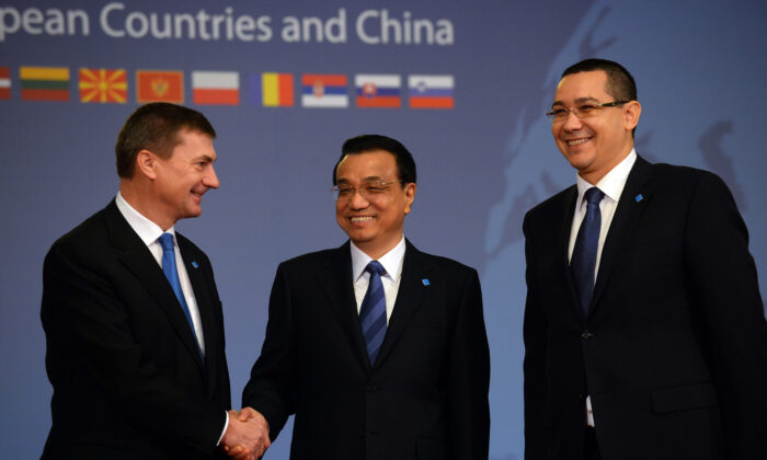 "Estonian Prime Minister Andrus Ansip (L) is welcomed by Chinese Prime Minister Li Keqiang (C) and Romanian counterpart Victor Ponta at the beginning of the ""Meeting of Heads of Government of Central and Eastern European Countries and China"" at the Parliament palace in Bucharest on Nov. 26, 2013. (Daniel Mihailescu/AFP via Getty Images)"