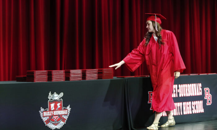 A student picks up her diploma during a graduation ceremony at Bradley-Bourbonnais Community High School on May 6, 2020, in Bradley, Ill. The high school diploma is frequently seen as the doorway to other opportunities, including college and a job. (KAMIL KRZACZYNSKI/AFP via Getty Images)