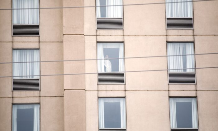 A guest is seen in a hotel window in Mississauga, Ont. by the Pearson International Airport on Feb. 22, 2021 as new air travel rules come into effect in Canada. (Cole Burston / The Canadian Press)