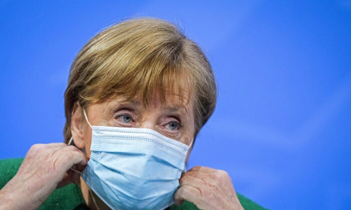 German Chancellor Angela Merkel holds her mask at a news conference after a meeting with state leaders to discuss options beyond the end of the pandemic lockdown, amid the outbreak of the coronavirus disease (COVID-19), in Berlin, Germany, on March 23, 2021. (Michael Kappeler/Pool via Reuters)